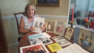 Nancy McCrory holds a diary with photos of her grandparents on the cover