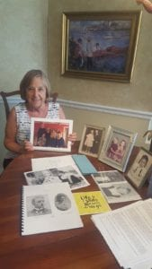 Nancy McCrory holds a family photo surrounded by other archives from her family's history