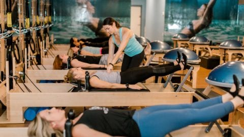 A Club Pilates instructor works with clients