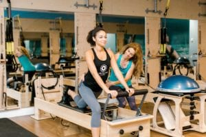Club Pilates owner Shannon Willits (right) helps people learn to stretch