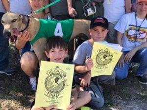 Greyson and Landon Fiese hold programs from the final greyhound race
